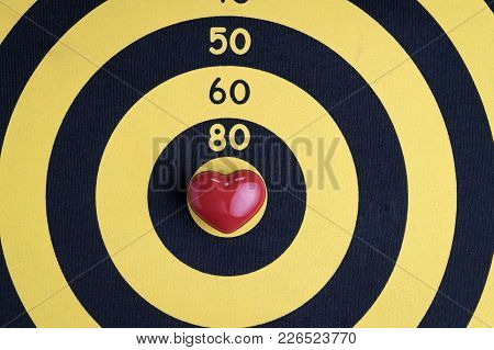 Love Target Background With Shiny Red Heart Shape On Center Of Cupid Archery Yellow Dartboard.