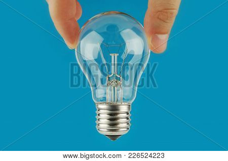 Hand Holding A Light Bulb With Blue Background. Concept And Idea Background.