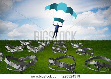 Businessman falling into trap on parachute
