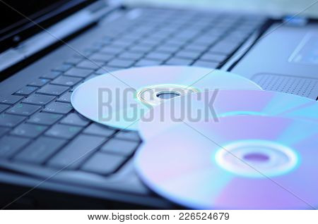 Three Dvd Disk On A Laptop Keyboard.