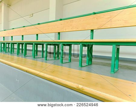 Rows Of Empty Wooden Benches In School Sporting Hall.  Tribune In Gym For Fans Of Matches With Empty