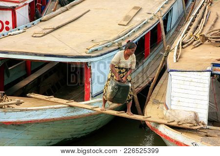 Mandalay, Myanmar - December 30: Unidentified Woman Carries Heavy Can To The Boat At Ayeyarwady Rive