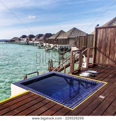 Pool At Balcony With Water Villas Background