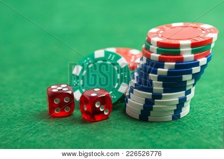 casino chips and dice on a green felt as background