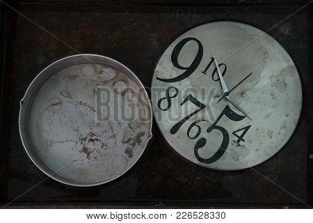 Gray Round Clock With A Dirty Dial And Asymmetrically Arranged Black Numbers Next To A Round Gray Bo
