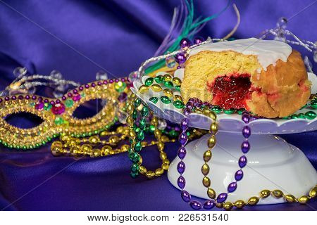 Close Up Of Jelly Filled Paczki With Mardi Gras Beads And Mask On Purple Satin
