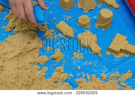 Kid Making Different Shapes By Sand With Moulds