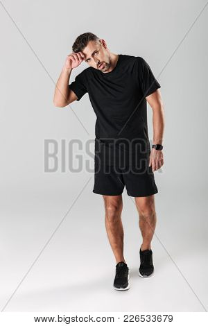 Full length portrait of a tired mature sportsman resting after unning isolated over gray background