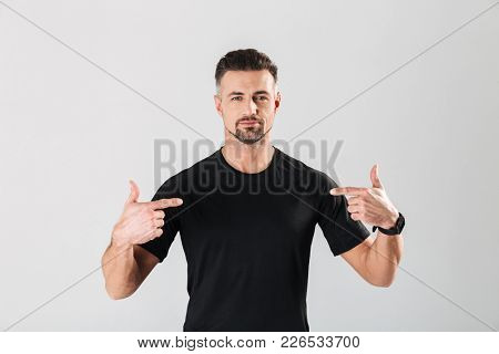 Portrait of a handsome mature sportsman pointing fingers at himself isolated over gray background