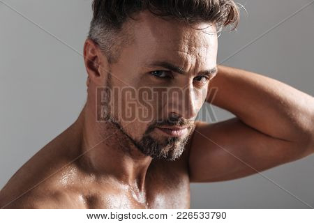 Close up portrait of a muscular mature shirtless sportsman posing and looking at camera isolated over gray background
