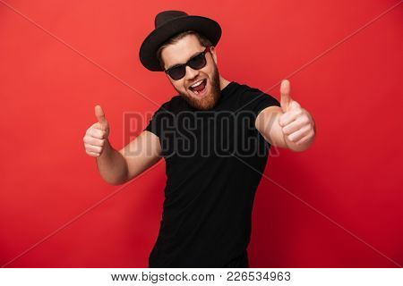 Image of excited young guy wearing black sunglasses and hat smiling and pointing fingers on camera meaning hey you isolated over red wall