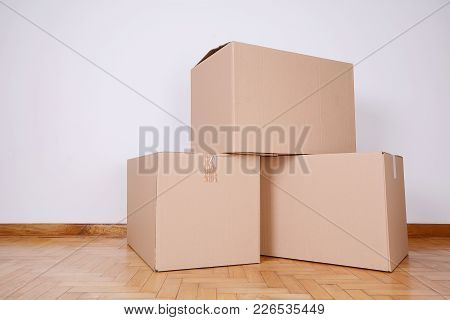 Stack Of Cardboard Boxes In The Empty Room. Moving Concept