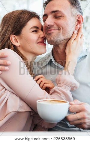 Joyful married couple hugging and having fun together in cozy city cafe with public display of affection