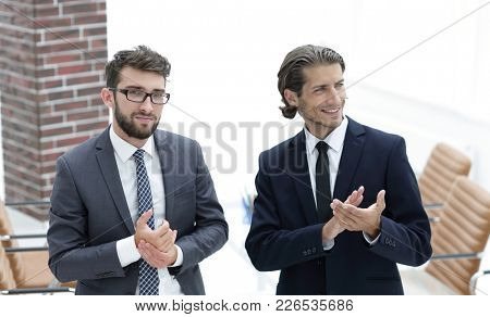 business partners applauding ,standing in the office