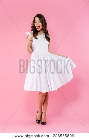 Full length portrait of a surprised young asian woman dressed in white dress looking at mobile phone isolated over pink background