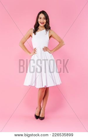 Full length portrait of a smiling young asian woman dressed in white dress posing while standing isolated over pink background