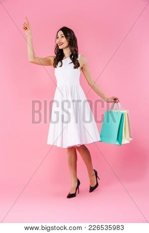 Portrait of a smiling young asian woman dressed in white dress holding shopping bags and waving hand isolated over pink background