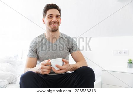 Photo of pleased morning man in t-shirt smiling while sitting in bedroom and drinking tea or coffee