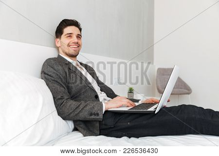 Photo of optimistic man in businesslike clothes smiling and looking aside while lying in bed with laptop