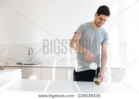Photo of muscular man in casual t-shirt making tea with pouring hot water into cup while having breakfast in morning at home