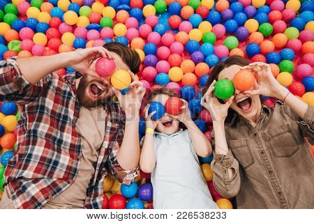 Image of emotional little child have fun with his parents in entertainment game center covering eyes with toy balls.