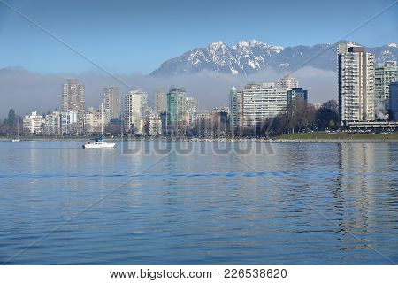 English Bay, Coast Mountains, Sailboat. A Sailboat Crosses English Bay. In The Background Are The Sn