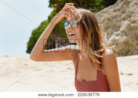 Outdoor Shot Of Positive Pretty Female In Swimsuit And Shades, Sunbathes At Seashore, Poses Against