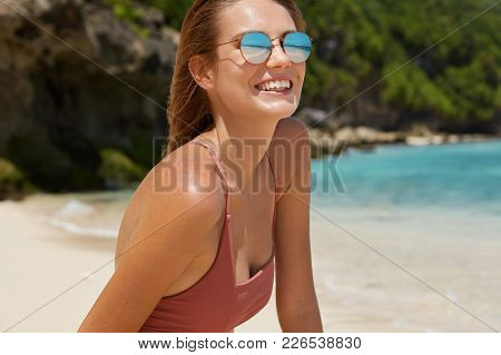 Cropped View Of Beautiful Suntanned Slender Young Woman In Swimsuit And Shades, Has Cheerful Express