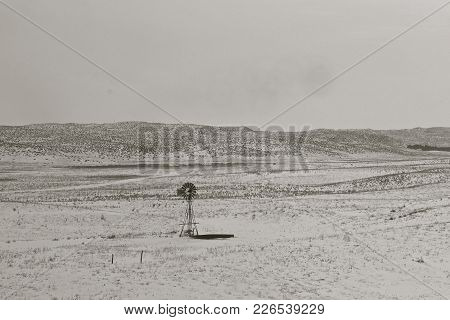 A Lone Old Windmill And Water Tank Stand Forlorn On A A Foggy Wintry Prairie Scene After A Snowfall