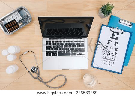Top View Of Doctor Desk Table With Stethoscope And Notebook With A Visual Test Chart