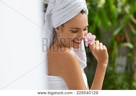 Relaxed Young Female With Soft Skin, Wrapped In Towel, Smells Beautiful Exotic Flower, Feels Relaxat