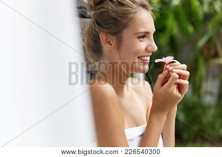 Relaxed Carefree Young Female With Happy Expression Wrapped In Towel, Dreams About Something Pleasan
