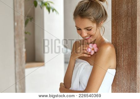 Beautiful Young Woman With Soft Skin, Has Light Hair Tied In Knot, Wears White Towel After Taking Do