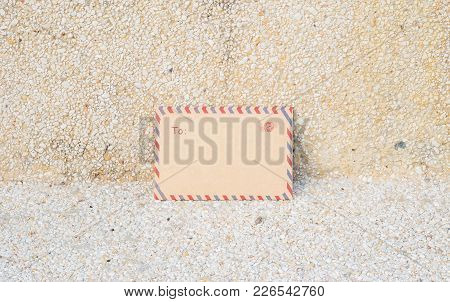 Closeup Brown Envelope On Blurred Stone Floor And Wall Textured Background