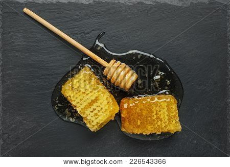 Golden Honeycomb And Honey Stick On A Black Stone Slate Plate.  Top View