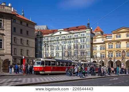 Prague, Czech Republic - March 16, 2017: An Old Red Tramway At A Station With People Waiting