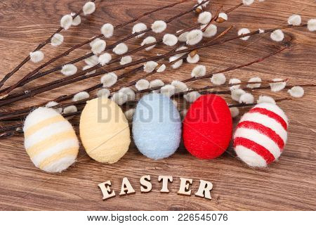 Colorful Eggs Wrapped Woolen String And Easter Catkins As Festive Decoration On Rustic Board