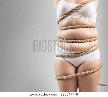 Fat Woman In White Underwear Twisted With A Rope. Copy Space. Obesity Concept. Over Gray Background.