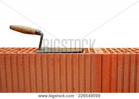 Trowel On Brick Wall On White Background. Masonry Tools.