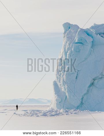 A Person Stands Near An Iceberg On The Frozen Surface Of The Ross Sea In Antarctica