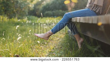 Woman sitting on wooden path and swing legs at the edge