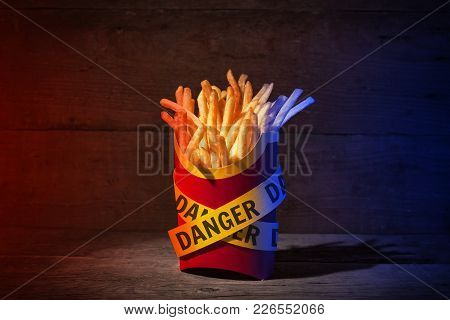 French Fries In A Red Packing Box On A Wooden Table With Yellow Police Ribbons With The Word Danger