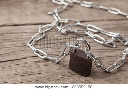 Closed Lock With A Chain Stands On An Old Wooden Table