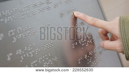 Blind reading on Braille at outdoor directory