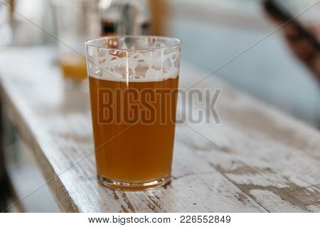 Close Up Of Glass Of Cold Beer On Old Wooden White Painted Table With Copyspace