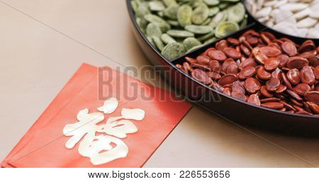 Traditional chinese snack tray with red packet of word meaning luck