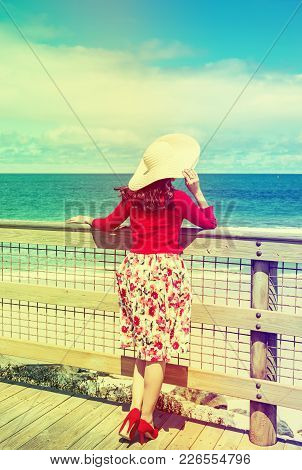 Beautiful Woman In Red Standing And Looking To The Sea  In Retro Style