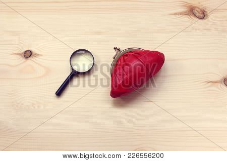 Red Purse And Magnifying Glass Lie On Flat Wooden Surface Top View / Search And Storage Of Invests