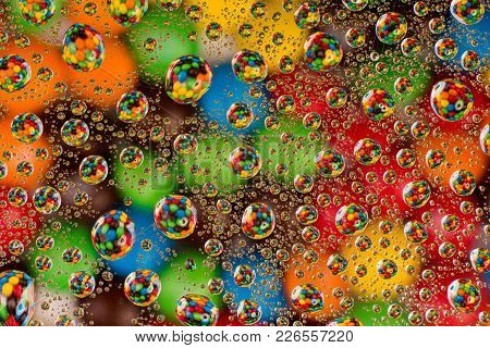 Creative Colorful Background. Colorful Candy Through Water Drops On Glass