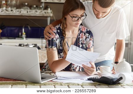 Cropped View Of Attractive Young Female And Man Study Bank Papers Attentively, Going To Take Loan Fo